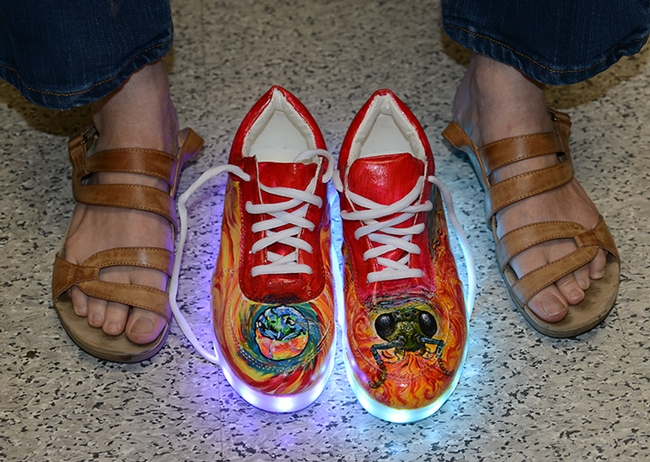 Lynn Kimsey gets ready to lace up her new shoes, painted with cuckoo wasps. (Photo by Kathy Keatley Garvey) for Bug Squad Blog