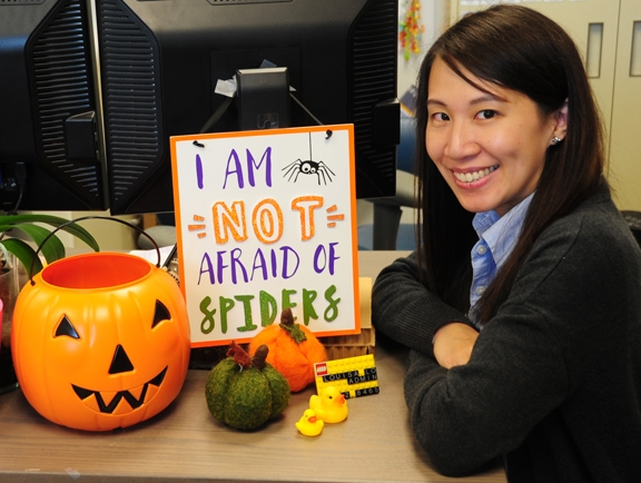 Louisa Lo, executive administrative assistant for Bruce Hammock, distinguished professor of entomology, sits next a sign proclaiming she is not afraid of spiders. She is. (Photo by Kathy Keatley Garvey)