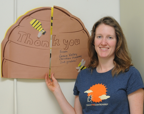ELIZABETH FROST, staff research associate and beekeeper at the Harry H. Laidlaw Jr. Honey Bee Research Facility, UC Davis, displays the clever thank-you card made by second graders at the Grace Valley Christian Academy, Davis. (Photo by Kathy Keatley Garvey)