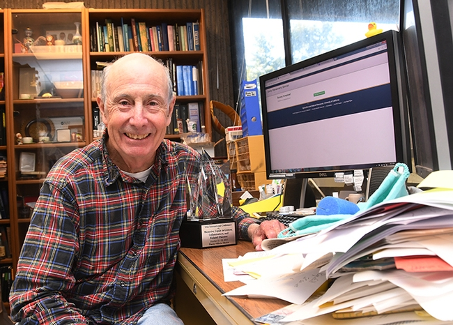 Bruce Hammock in his office in Briggs Hall, UC Davis, with his outstanding achievement award from the Eicosanoid Research Foundation. (Photo by Kathy Keatley Garvey)