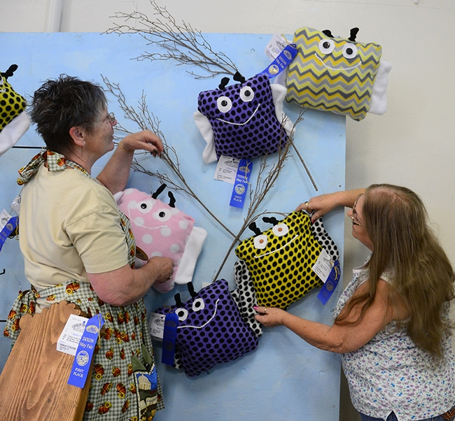Dixon May Fair Youth Building superintendent Building superintendent Stephanie Hill (left) of Yuba City and assistant building superintendent Pat Connelly of Vacaville hang bumble bee pillow, the work of Solano County 4-H'ers. (Photo by Kathy Keatley Garvey)