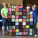 See the bumble bee on the aghan (top row)? This Minnesota sample afghan is the work of Debra Holter of San Pablo. Holding it are McCormack Hall superintendent Gloria Gonzalez (right) and assistant Kara Payne. (Photo by Kathy Keatley Garvey)