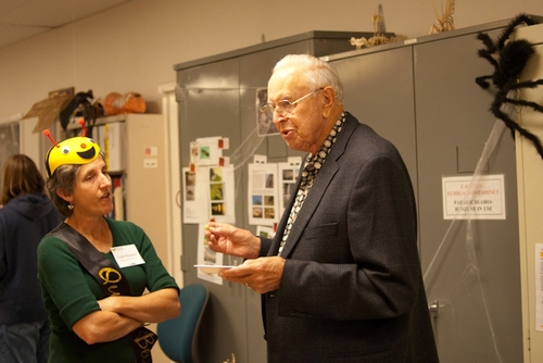 QUEEN BEE Lynn Kimsey, director of the Bohart Museum of Entomology and professor and former chair of the UC Davis Department of Entomology, chats with emeritus professor and entomologist Oscar Bacon of Davis, also a former chair of the department. A black widow spider hovers in the background. (Photo by Louie Yang)