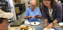 Tabatha Yang, education and outreach coordinator for the Bohart Museum of Entomology, serves dessert at Robbin Thorp's birthday celebration while the distinguished emeritus professor reads the birthday wishes. (Photo by Kathy Keatley Garvey) for Bug Squad Blog