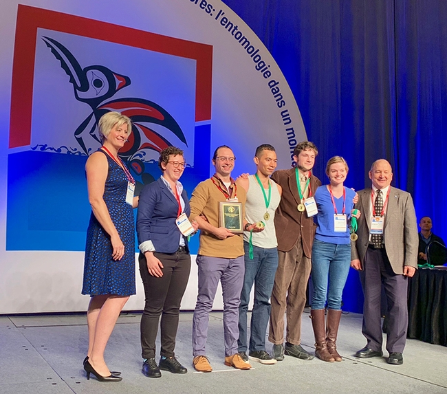 Gamemaster Deane Jorgensen (far left), research scientist at Sygenta, and ESA president Michael Parrella (far right), dean of the College of Agricultural and Life Sciences,  University of Idaho, flank the national Linnaean Games Team champions. In the center (from left) are Emily Bick, Brendon Boudinot, captain Ralph Washington Jr., Zachary Griebenow and Jill Oberski. Parrella is a former professor and chair of the UC Davis Department of Entomology and Nematology. (Joe Rominiecki Photo)