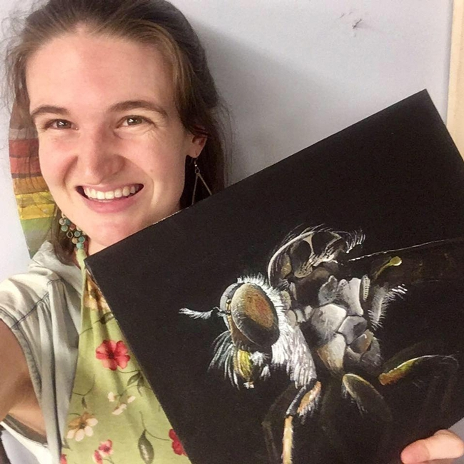 UC Davis fourth-year doctoral student Charlotte Herbert Alberts holds her acrylic painting of an  Assassin fly (Ommatius sp.) that she painted to celebrate World Robber Fly Day, April 30.