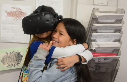 Brownie Girl Scout Jayda Navarette (left), 8, of Vacaville, is comforted by Keira Yu, 8, of Vacaville as the spiders come into view in a virtual reality demonstration at the Bohart Museum of Entomology. (Photo by Kathy Keatley Garvey)