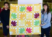 Gloria Gonzalez, superintendent of McCormack Hall at the Solano County Fair, holds a bee-themed quilt with assistant Jarod Fernander of Vallejo, 15, a student at the Pleasant Hill Adventist Academy. The quilt is the work of Tina Frothy of Vallejo. (Photo by Kathy Keatley Garvey)