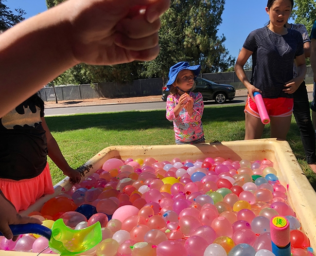 Some 2000 colorful water balloons are ready to be tossed. In the background is water warrior Lea Barnych, 4, whose mother Natalia Vasylieva is a researcher in the Bruce Hammock lab. (Photo by Kathy Keatley Garvey)
