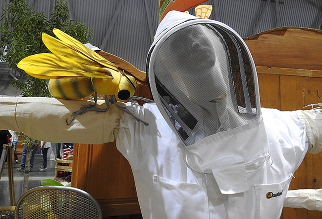 A gigantic honey bee on the arm of a beekeeper mannequin in Building B of the California State Fair. (Photo by Kathy Keatley Garvey)