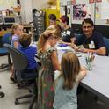 Visiting scholar Syed Fahad Shah and doctoral student Charlotte Herbert Alberts (next to him) help youngsters make buttons at the Bohart Museum of Entomology open house. (Photo by Kathy Keatley Garvey)