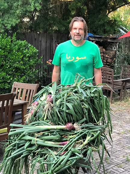 Agricultural entmologist Christian Nansen of the UC Davis Department of Entomology and Nematology with onions harvested from his garden.