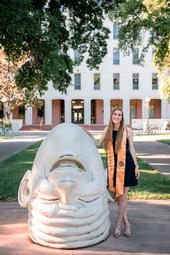 UC Davis fourth-year student Jessica Macaluso stands next to artist Robert Arneson's egghead sculpture in front of Mrak Hall. She will receive her bachelor's degree in psychology this fall.