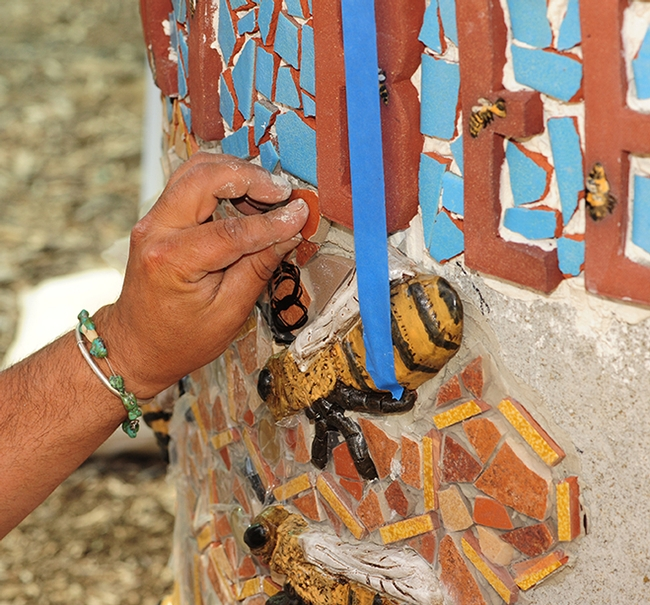 The hands of Mark Rivera as he works to install art projects at the Häagen-Dazs Honey Bee Haven at UC Davis. (Photo by Kathy Keatley Garvey)
