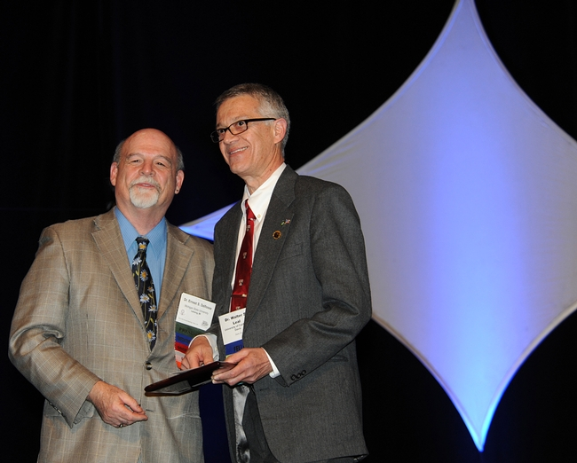 UC Davis professor Walter Leal (right) receives the Nan-Yao Su Award from ESA President Ernest Delfosse. (Photo by Kathy Keatley Garvey)
