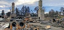 In a Santa Rosa neighborhood, all homes were burned down to the foundations with only things like fireplaces, washer dryer sets, and car frames left. Photo by Faith Kearns. for The Confluence Blog