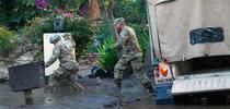 California National Guard members wade through mud to people trapped inside a Montecito home. Air National Guard photo by Senior Airman C. Housman. for The Confluence Blog