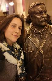 Doctoral student Rebecca Godwin won first place for her poster at the American Arachnological Society. This is Godwin with a statue of Theodore Roosevelt in the American Museum of Natural History. She was doing some work in the archives there for the Ummidia revision.