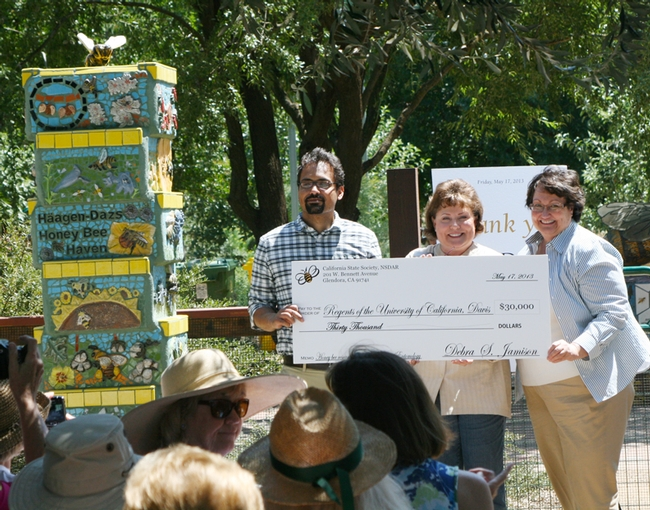 Bee scientist Brian Johnson, assistant professor of entomology, UC Davis Department of Entomology and Nematology, receives a $30,000 check from Debbie Jamison (center) of Fresno, State Regent of California State Society of the Daughters of the American Revolution and Karen Montgomery of Modesto, chair of the state regent's project. (Photo by Martha Ozonoff)