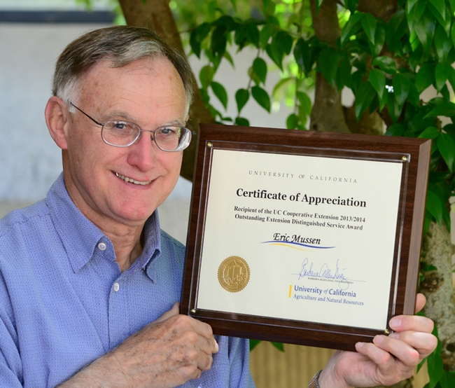 Eric Mussen with UC ANR plaque. (Photo by Kathy Keatley Garvey)