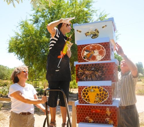 Diane Ullman, Donna Billick and Eric Mussen install a beehive column.