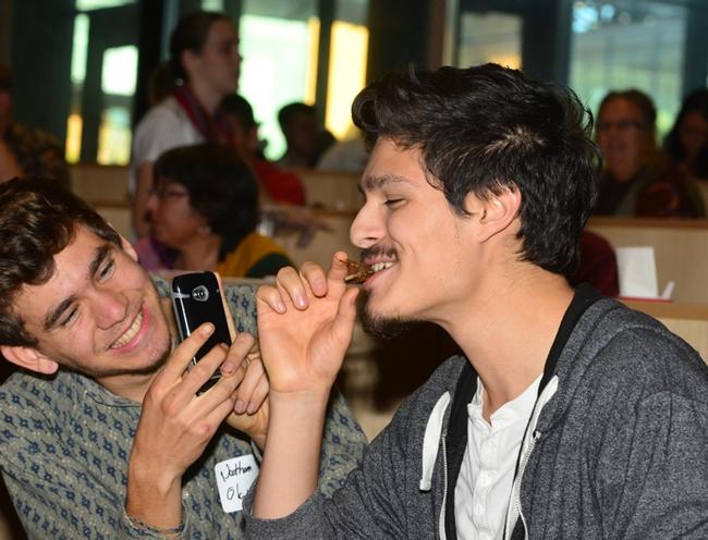 Josh Bubar, a UC Davis microbiology major, takes a photo of his friend, Nathan Olguin, eating a bug