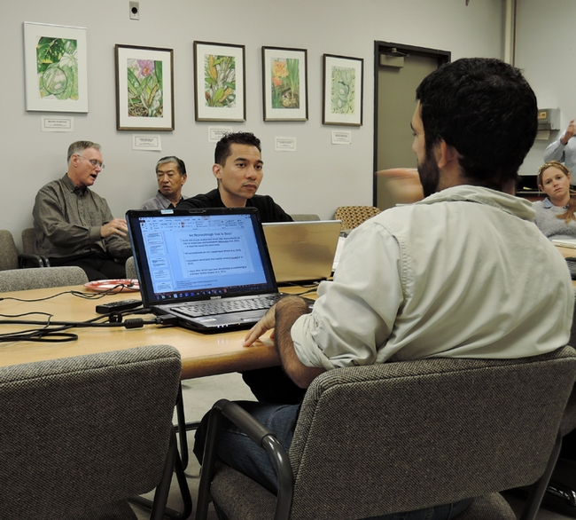 Ralph Washington Jr. (center) listens to the discussion. In the background are advisors Eric Mussen (left), retired Extension apiculturist, and Dave Fujino, director of the California Center for Urban Horticulture.