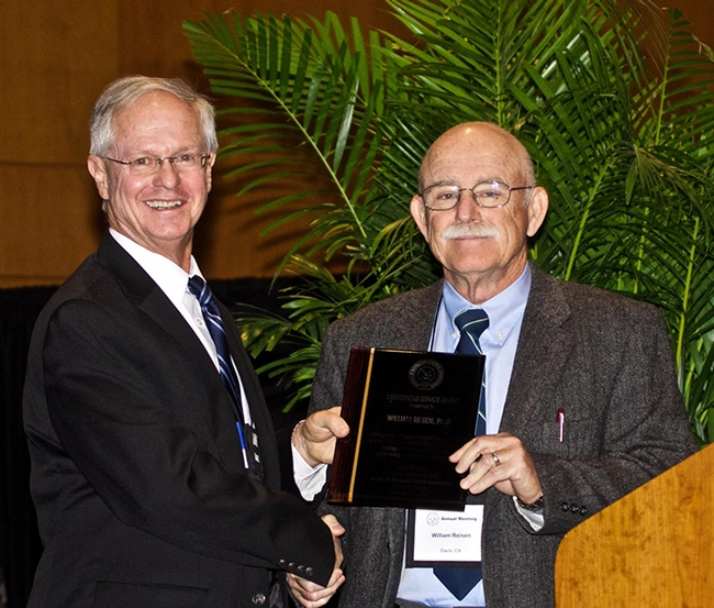 AMCA President Kenneth Linthicum (left), director of the Center for Medical, Agricultural and Veterinary Entomology, USDA-Agricultural Research Service, presents the Meritorious Service Award to medical entomologist William Reisen. (Photo by Rick Duhrkopf)