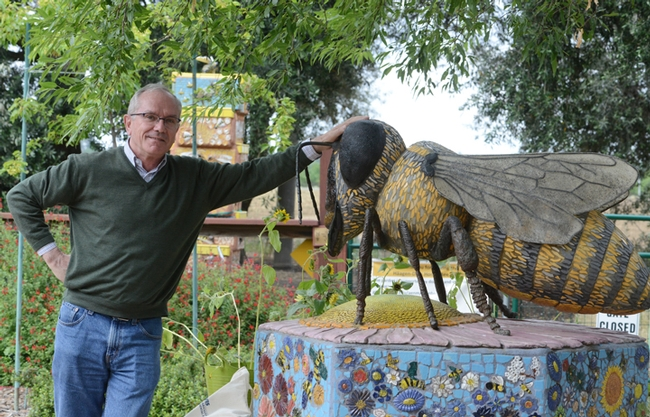 Yves Le Conte stands next to the six-foot-long ceramic mosaic bee sculpture that anchors the Häagen-Dazs Honey Bee Haven. It is the work of artist Donna Billick. (Photo by Kathy Keatley Garvey)
