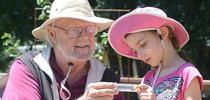 Robbin Thorp, UC Davis distinguished emeritus professor of entomology, shows a bee to a visitor at the 2016 TODS Day at the Häagen-Dazs  Honey Bee Haven. This is Lalibella Eaves, then 6, daughter of Professor Valerie Fournier of Laval University, Quebec City. Her mother was a visiting scholar in the Neal Williams lab. (Photo by Kathy Keatley Garvey) for Entomology & Nematology News Blog