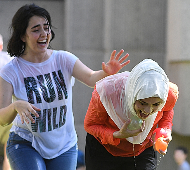 Medical researchers Israa Aliawad (left) and Liyan Afaneh of Aldrin Gomes lab delight in the water battle. (Photo by Kathy Keatley Garvey)