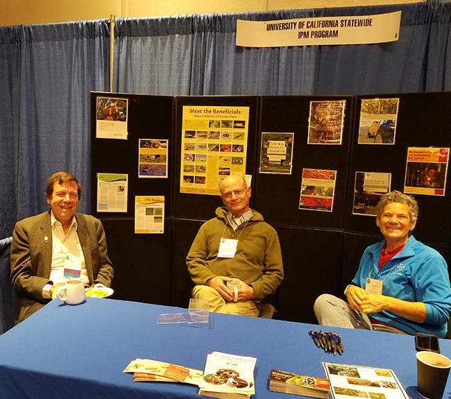 Lifetime achievement award winners Frank Zalom (left) and Pete Goodell share a moment in the UC IPM booth with Cheryl Wilen, Area IPM Advisor and IPM Extension Coordinator for Natural Resources. (Photo by Lena McBean, Remsberg Inc.)