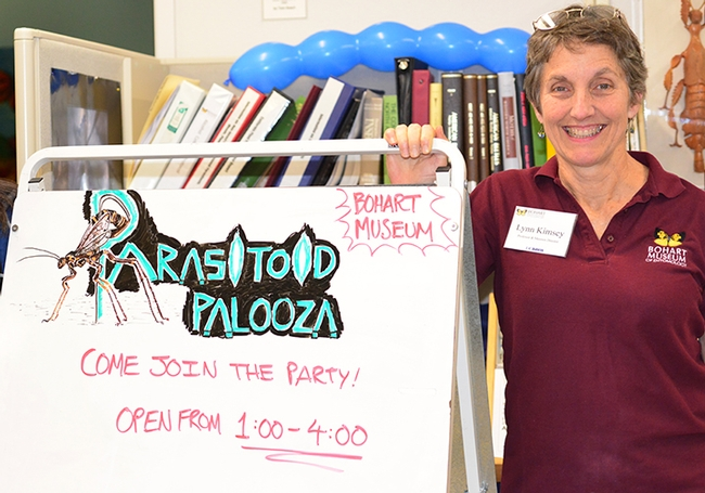 Lynn Kimsey, director of the Bohart Museum of Entomology, stands by a Parasitoid Palooza sign. (Photo by Kathy Keatley Garvey)