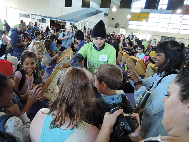 Enthusiasm runs high when the traveling display cases of Bohart Museum of Entomology specimens are introduced to the public. This image was taken at a Solano County Youth Agriculture Day on the Solano County Fairgrounds. This is Bohart associate Parris McGrath greeting the third-graders. (Photo by Kathy Keatley Garvey)
