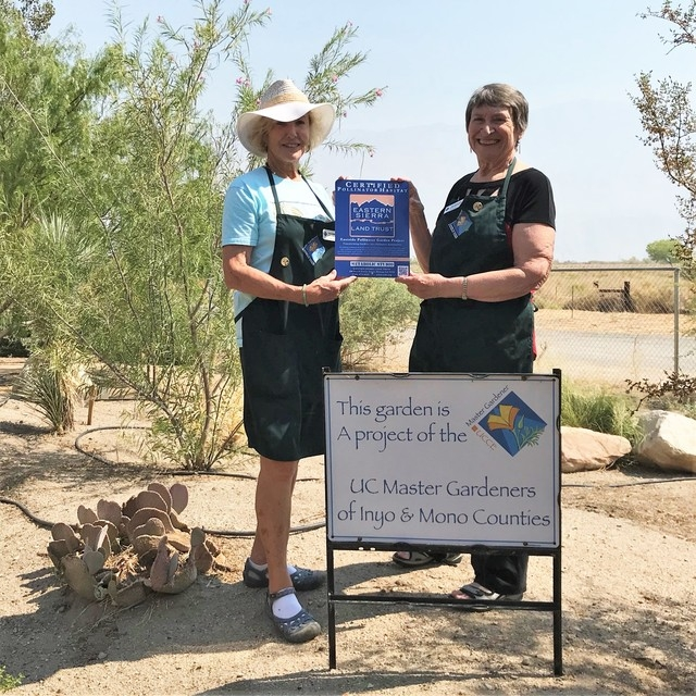Edie and Joanne standing in front of a garden sign holding their award.