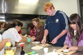 4-H participants learn to make sushi. Nutrition education is often a part of 4-H projects.