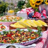 Photo of picnic foods, including corn & bean salad, on a picnic table.