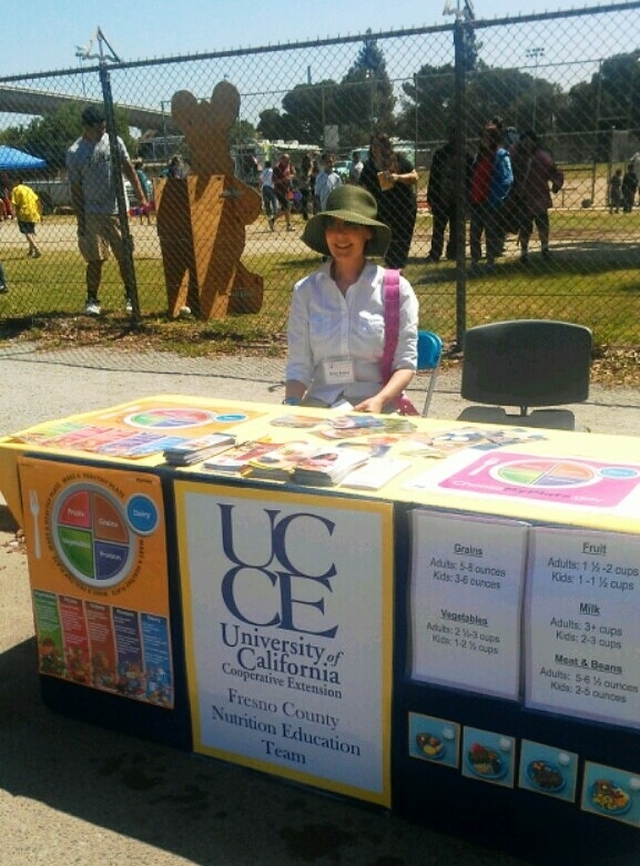 Volunteer Betsy Knapp sitting a Uc CalFresh educational booth at a recent event.