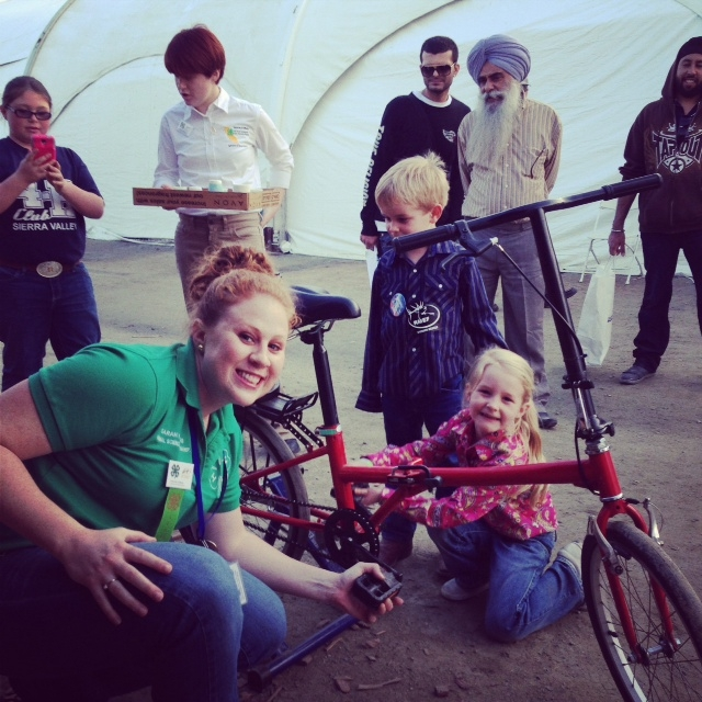 4-H program representative Sarah Watkins pushes pedals on the smoothie bike with a young visitor.