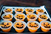 Orange fruit cups with jack-o-lantern faces drawn on the plastic.