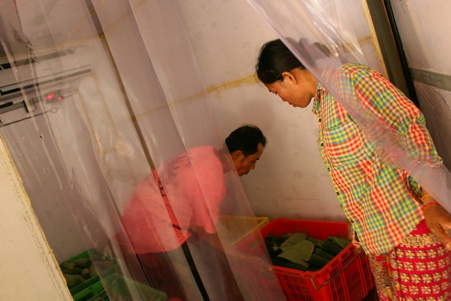 Man and woman carrying crate of vegetables into a doorway with strip curtains, with an air conditioner and CoolBot visible in the background.