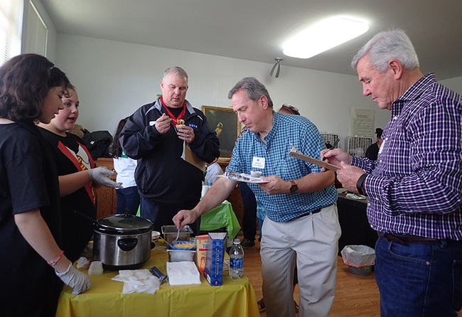 Isabel Martinez (left) and Trinity Roach of the Tremont 4-H Club watch as judges sample their chili. From left are Robert Reed of Benicia, Will Cant of Vallejo, and Solano County Board of Supervisor Skip Thomson of Dixon. (Photo by Kathy Keatley Garvey)