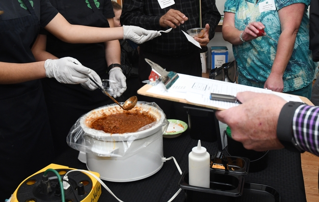 The scenario: crockpot of chili, gloved hands, spoons, and a judge's clipboard. (Photo by Kathy Keatley Garvey)