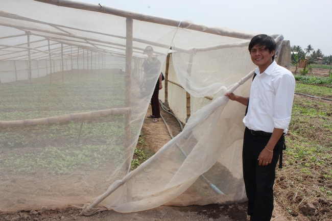Outside, a young man holds open a net door into a simple bamboo structure covered in thin netting. Inside the nets, a woman stands among the vegetable seedlings in the ground.