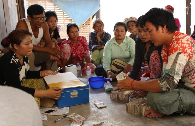 Cambodian group sits on the floor, watching as cash gets counted and recorded.
