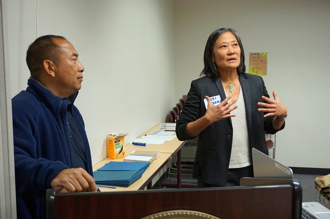 Patti Chang (right) of Feed the Hunger Foundation speaks to the group, UCCE ag assistant Michael Yang translates into Hmong.