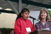 A fourth-grade student reads her winning garden essay as Linda Hahn looks on.