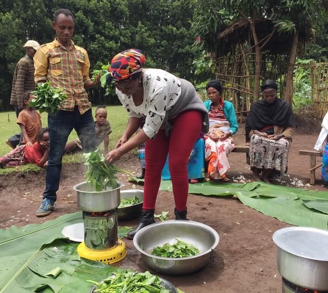 Man holds leaves and woman cooks leaves in a pot on a burner outside, with farmers gathered around.