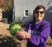 Elaine Silver, wearing sunglasses and a purple sweatshirt with Washington printed in white, holds up a green head of cabbage.