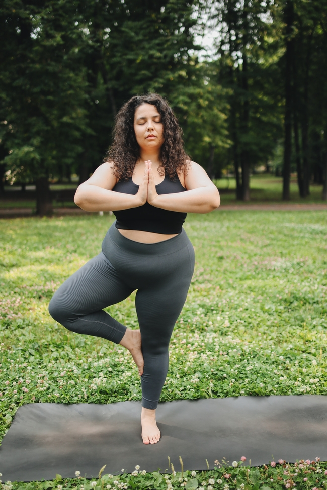 Woman in black sports bra and leggings on a doing yoga in a grass field
